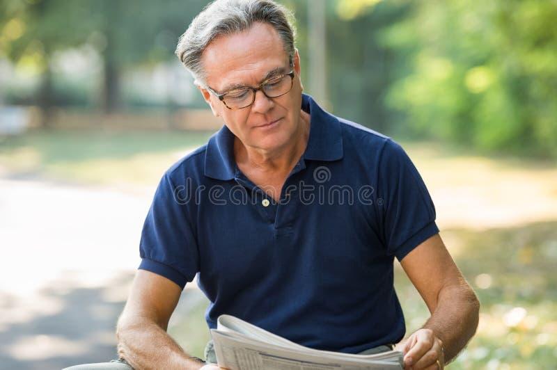 Jornal da leitura do homem sênior fotos de stock