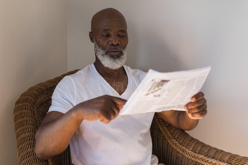 Jornal da leitura do homem sênior em casa foto de stock royalty free