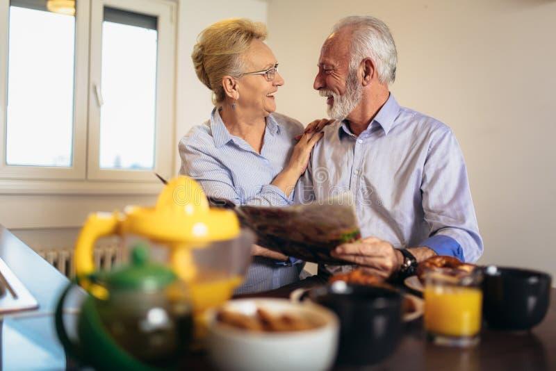 Jornal de amor envelhecido da leitura dos pares em casa foto de stock royalty free