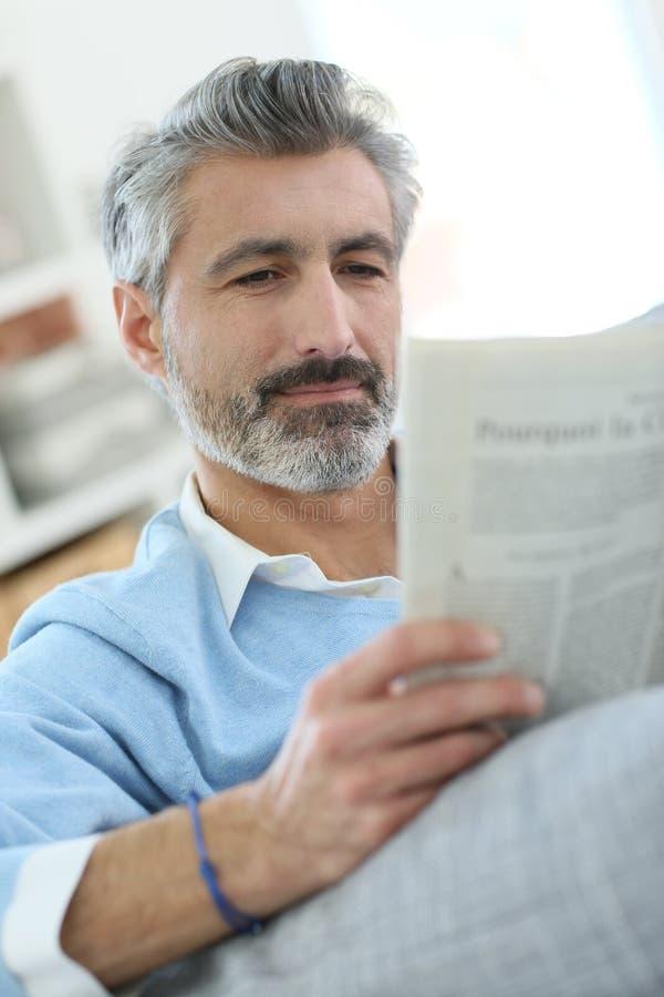 Jornal de meia idade da leitura do homem imagens de stock royalty free
