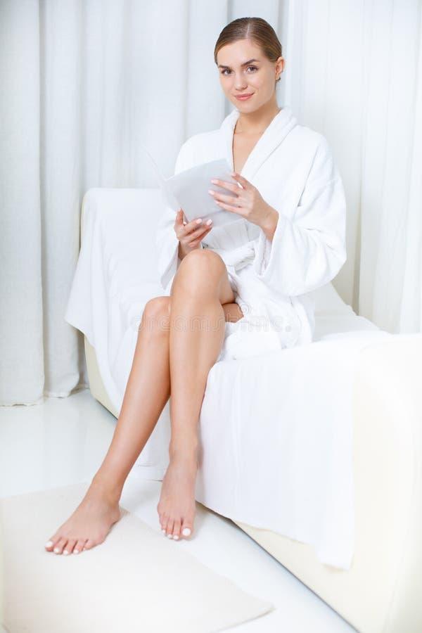 Jornal despreocupado da leitura da mulher na sala de estar dos termas imagem de stock royalty free
