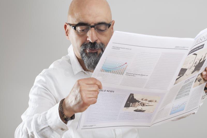 Jornal envelhecido médio da leitura do homem fotografia de stock