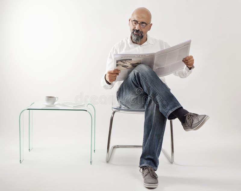 Jornal envelhecido médio da leitura do homem foto de stock