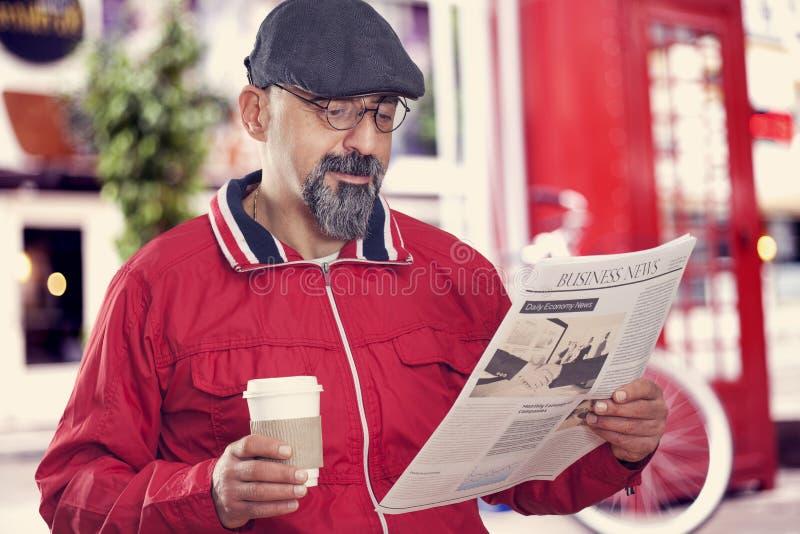 Jornal envelhecido médio da leitura do homem fotos de stock