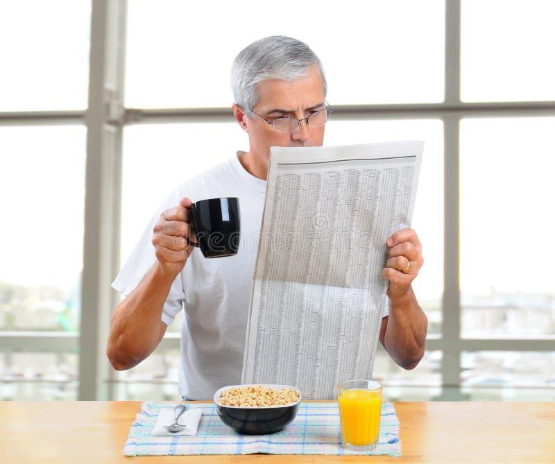 Jornal envelhecido médio da leitura do homem com pequeno almoço fotos de stock