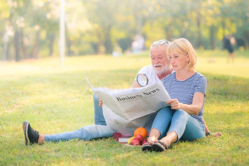 Jornal idoso da leitura dos pares no jardim no por do sol Amor da pessoa idosa dos pares do conceito fotos de stock