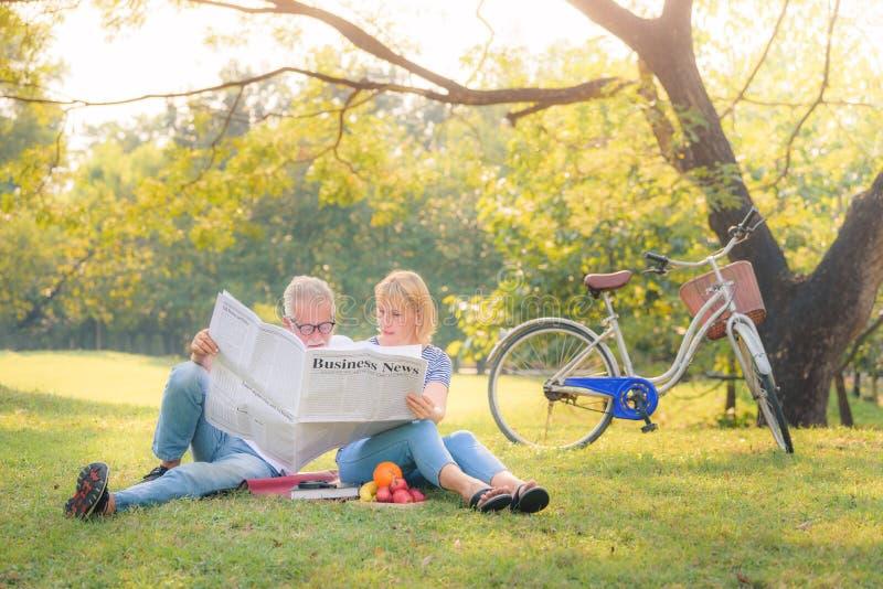 Jornal idoso da leitura dos pares no jardim no por do sol Amor da pessoa idosa dos pares do conceito foto de stock royalty free