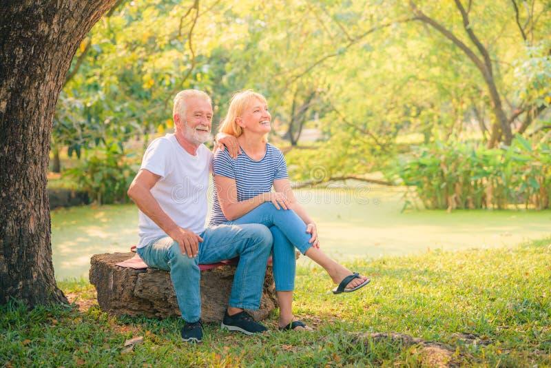 Jornal idoso da leitura dos pares no jardim no por do sol Amor da pessoa idosa dos pares do conceito fotografia de stock royalty free