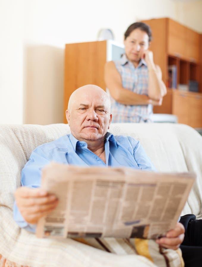 Jornal maduro da leitura do homem contra a mulher triste fotografia de stock royalty free