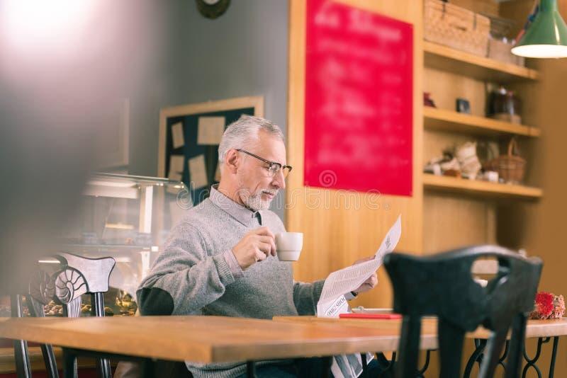 Jornal maduro farpado da leitura do homem de negócios e café bebendo imagens de stock royalty free