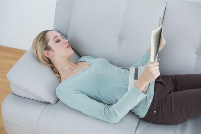 Jornal natural delgado da leitura da mulher que encontra-se no sofá fotografia de stock royalty free