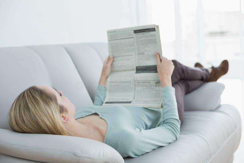 Jornal ocasional magro da leitura da mulher que encontra-se no sofá foto de stock royalty free