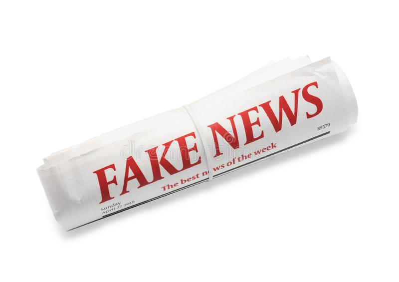 Jornal rolado com NOTÍCIA FALSIFICADA do título no fundo branco fotos de stock royalty free