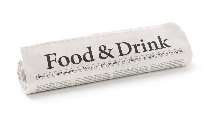 Jornal rolado com o alimento e a bebida do título foto de stock