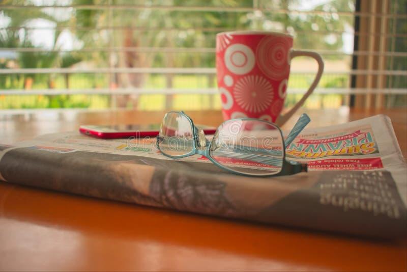 Jornal, vidros de leitura, telefone celular e uma xícara de café na tabela foto de stock