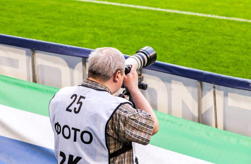Jornalista fotográfico perto do campo de futebol fotografia de stock royalty free
