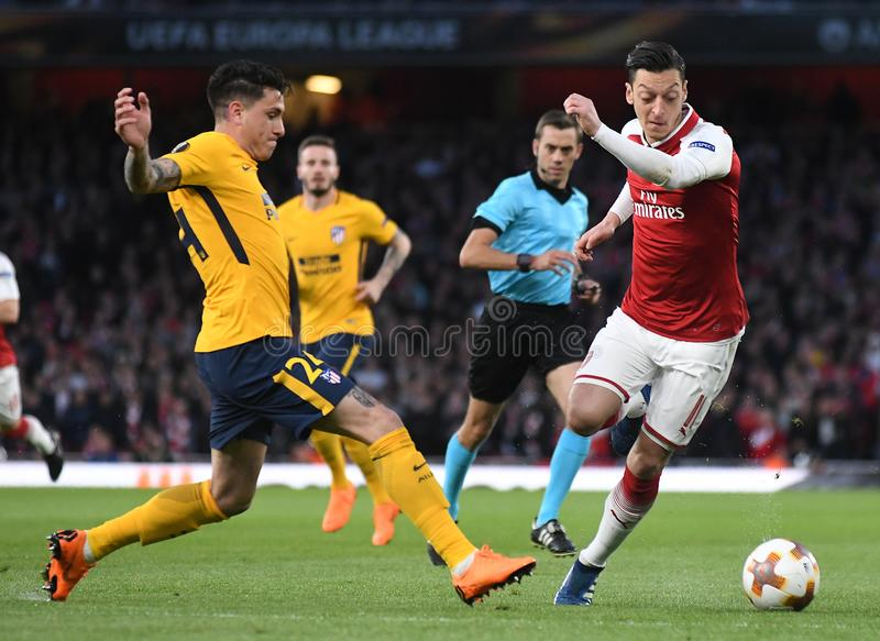 Jose Maria Gimenez and Mesut Ozil. Players pictured during the 2017/18 UEFA Europa League Semi-final 1st leg game between Arsenal FC and Atletico Madrid held on royalty free stock photography