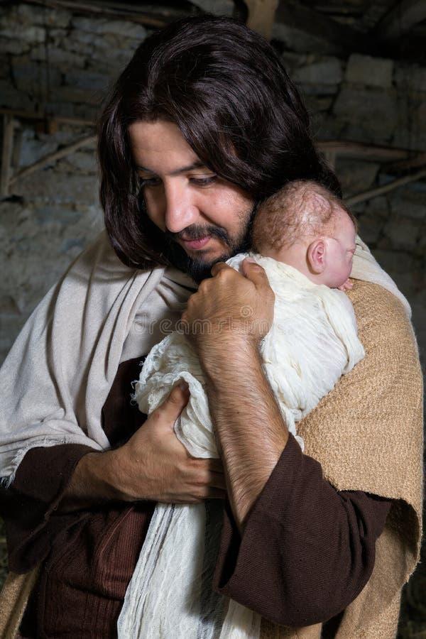 Joseph, der Baby Jesus umarmt lizenzfreies stockbild