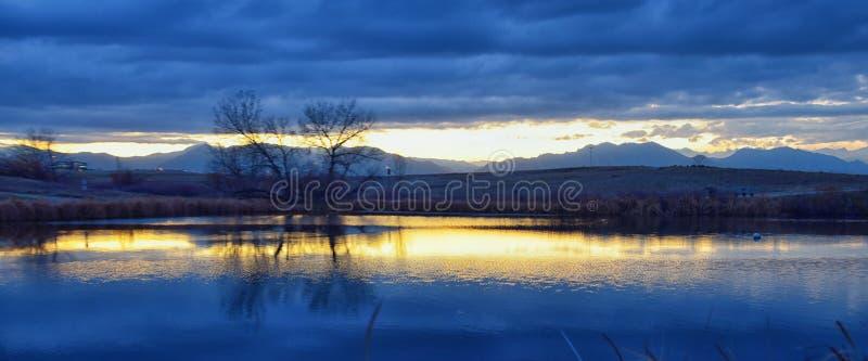 Josh's池塘人行道、反射的日落在布隆菲科罗拉多围拢由香蒲,平原和落矶山脉la看法  库存图片