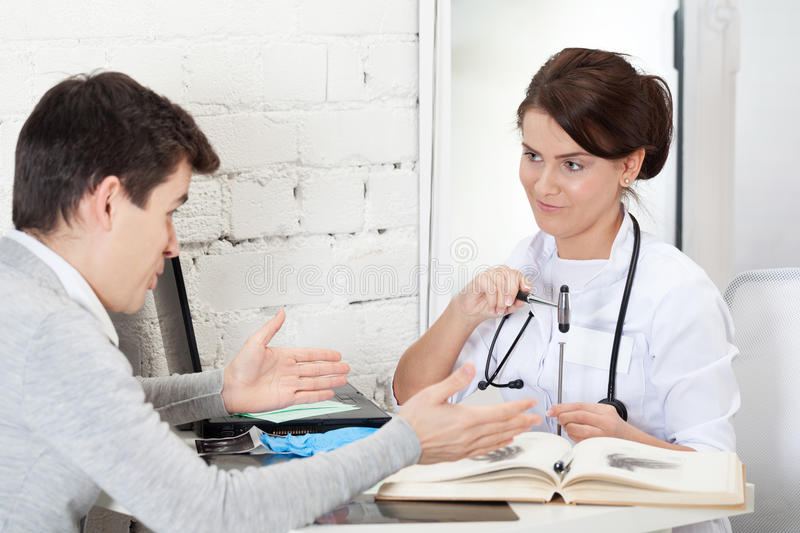 Joshing patient. Doctor joshing patient with reflex hammer and nail stock images