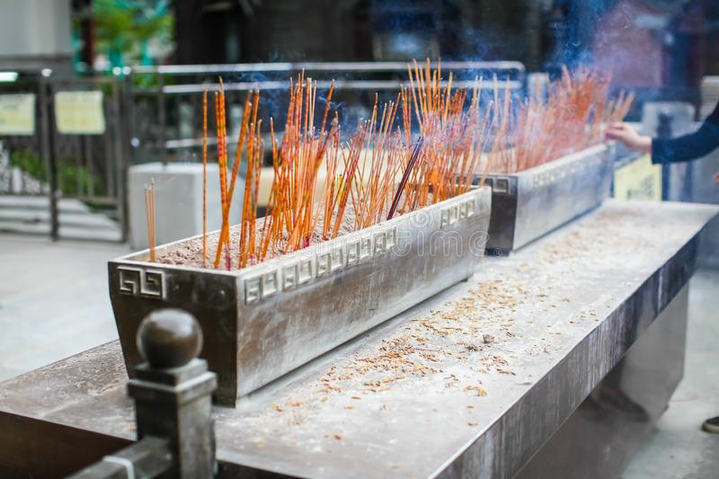 Joss sticks burning in sand tray in front of temple shrine, incense stick Asian traditional Chinese Buddhist temple royalty free stock photography