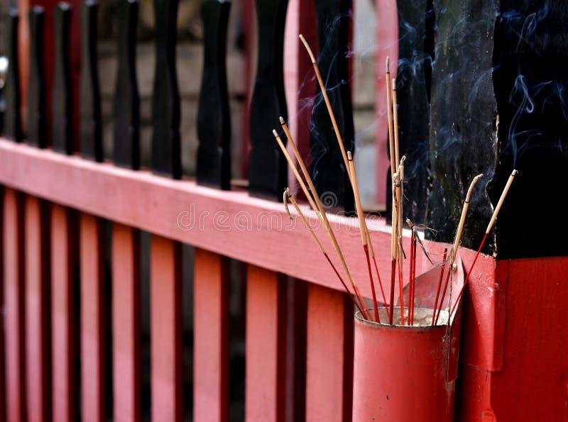 Josspinnar för ber respekt i templet arkivfoto