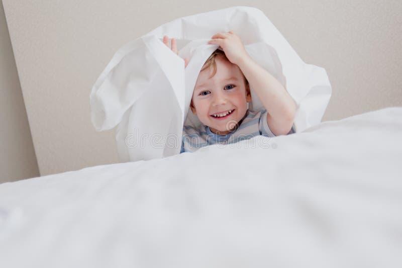 Jouant le cache-cache un petit garçon photo stock