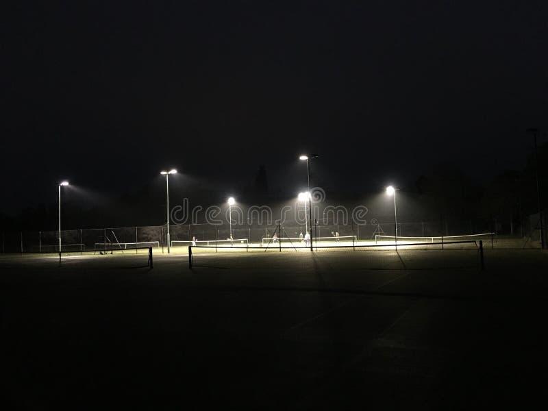 Jouant le tennis la nuit - le court de tennis s'est allumé la nuit photographie stock