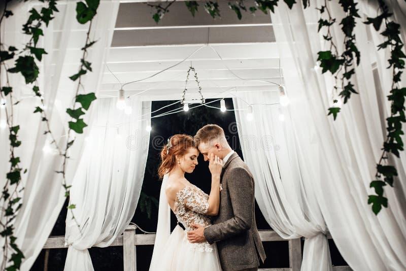 Joue du ` s de jeune mariée de baisers de marié tendre l'étreignant dans le jardin images libres de droits