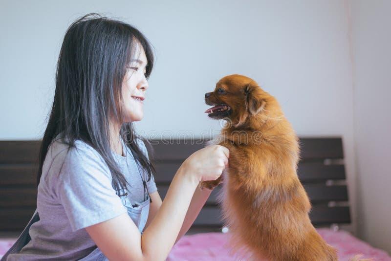 Jouer asiatique gai de fille de jeune adolescent et amusement heureux avec son chien à la maison photographie stock libre de droits