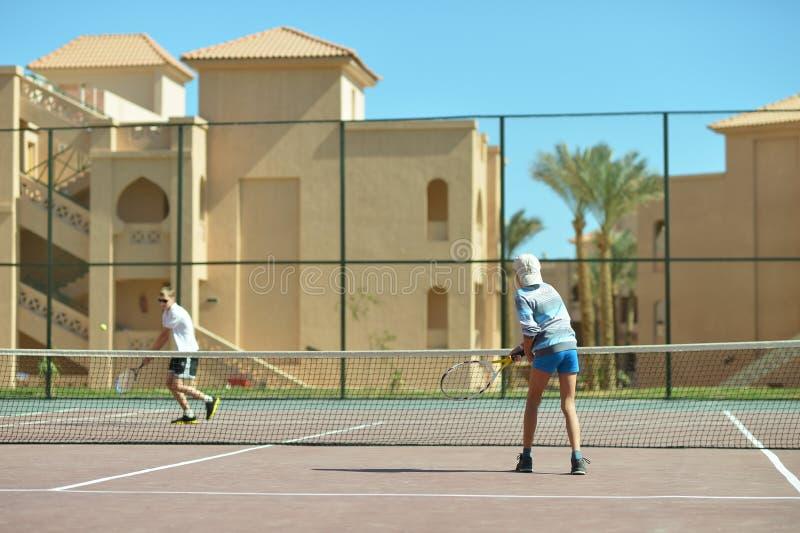 Jouer au court de tennis photo libre de droits