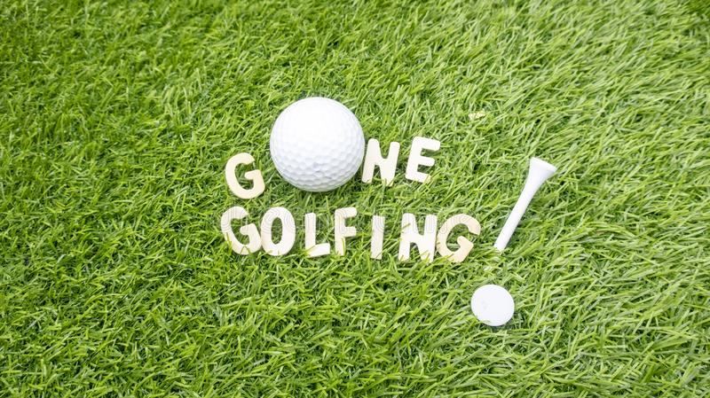 Jouer au golf ALLÉ est sur l'herbe verte photographie stock