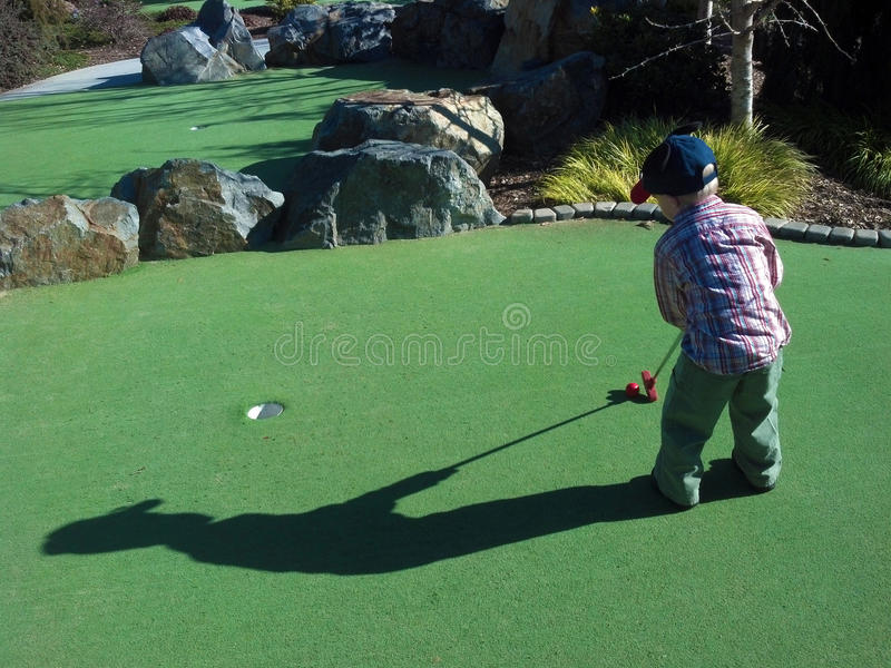Jouer au golf de petit garçon photos libres de droits