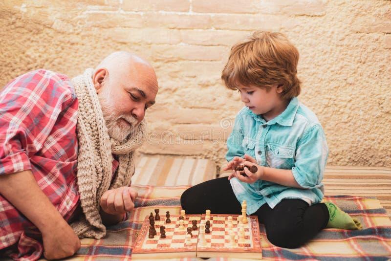 Jouer aux échecs Petit garçon jouant aux échecs avec son grand-père Chessman Échecs Petit garçon mignon jouant aux échecs photo stock