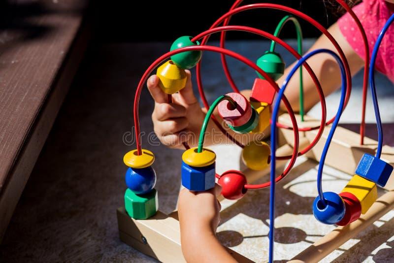 Jouer avec le jouet Bead Maze dans un jardin plus doux. Jouet pour enfants. Le labyrinthe des programmes en bois. Gosses photographie stock
