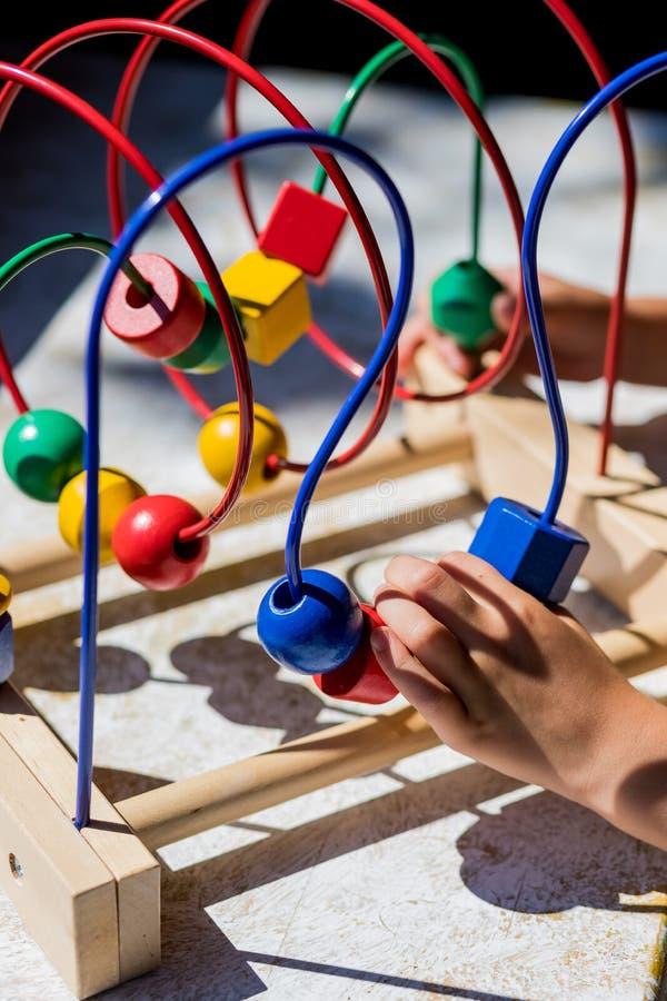 Jouer avec le jouet Bead Maze dans un jardin plus doux. Jouet pour enfants. Le labyrinthe des programmes en bois. Gosses image libre de droits