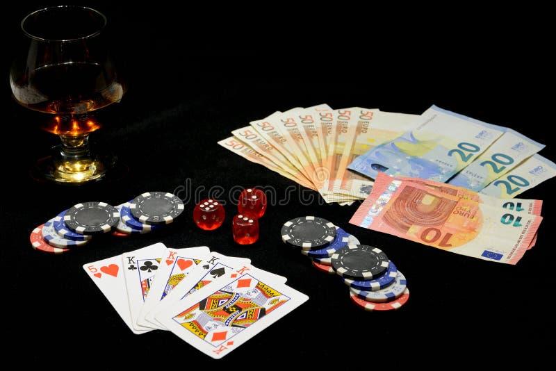 Jouer des cartes, des puces, des factures d'argent et un verre de cognac sur un fond noir image libre de droits