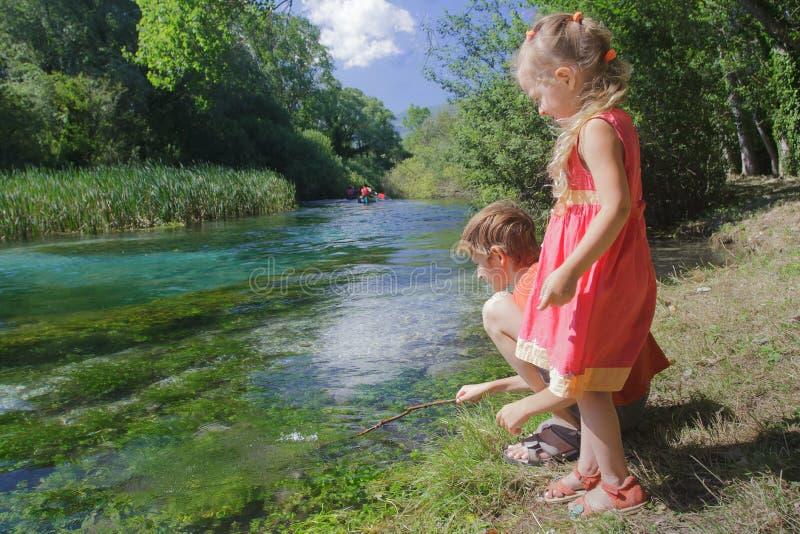 Jouer des enfants de mêmes parents et des sportifs kayaking flottant sur la rivière de Tirino photos stock