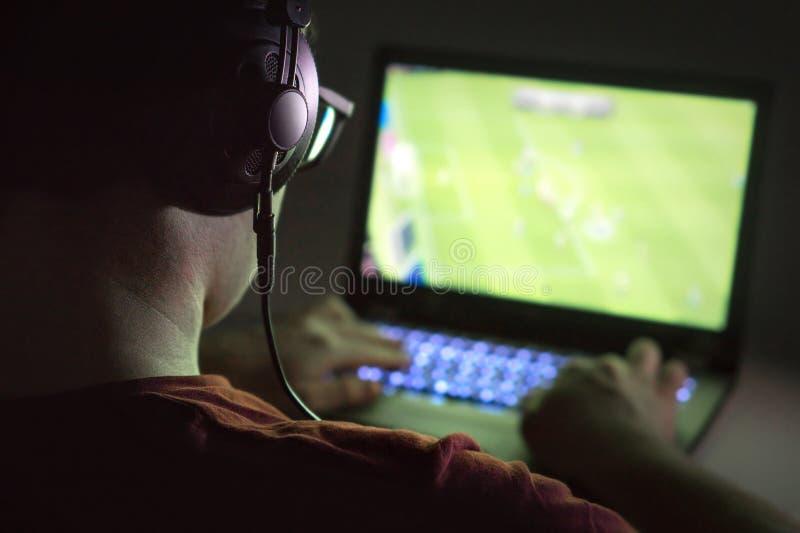 Jouer des jeux vidéo avec l'ordinateur portable Le jeune homme joue au football en ligne photographie stock
