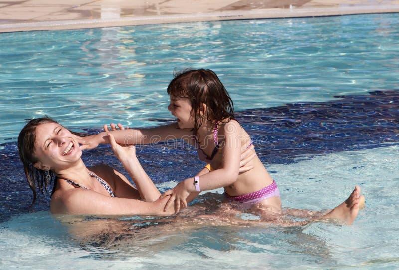 Jouer familly heureux dans la piscine images libres de droits