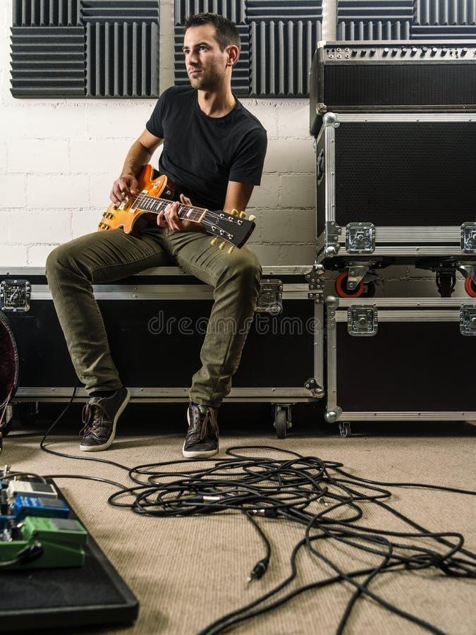 Jouer la guitare dans le studio de répétition image stock