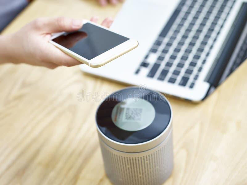 Jouer la musique par un haut-parleur portatif de bleu-dent photo stock