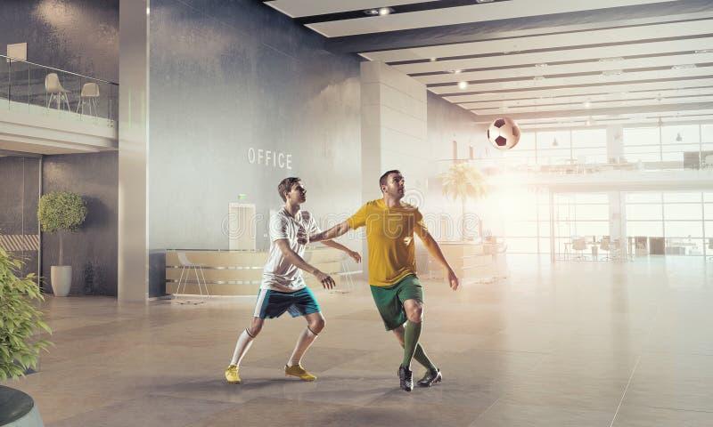 Jouer le football dans le bureau Media mélangé photo stock