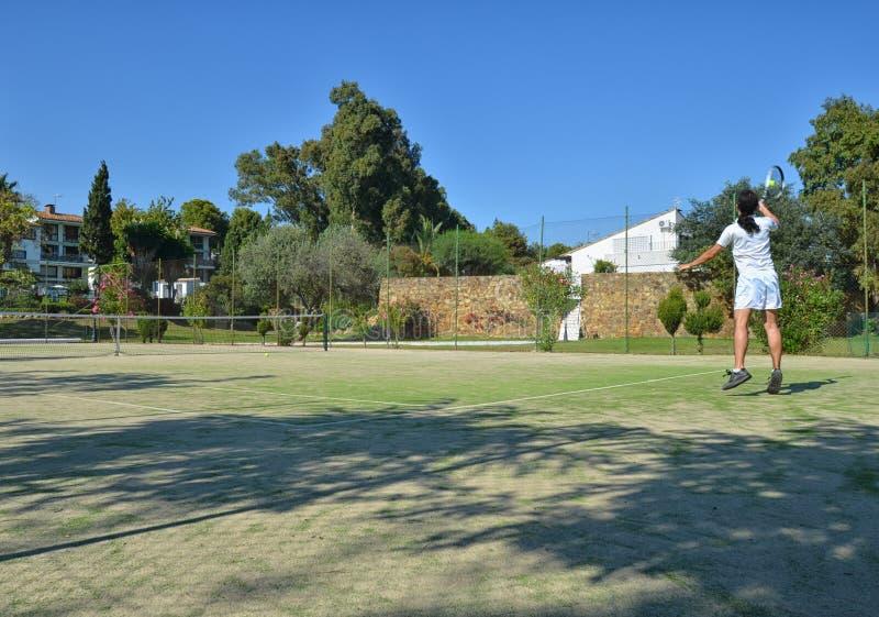 Jouer le tennis dans un jour ensoleillé photo libre de droits
