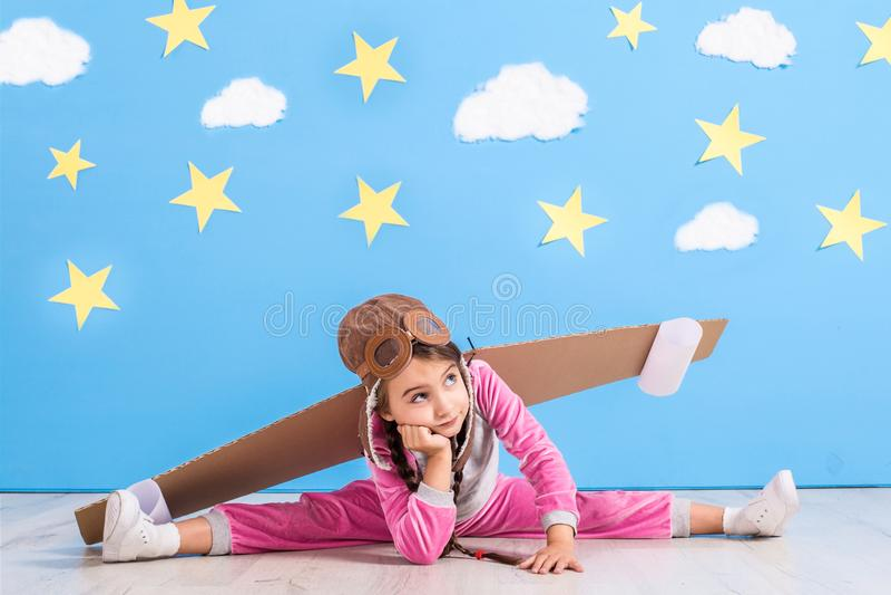Jouer pilote de fille avec le paquet de jet de jouet à la maison Succès et concept de chef photographie stock libre de droits