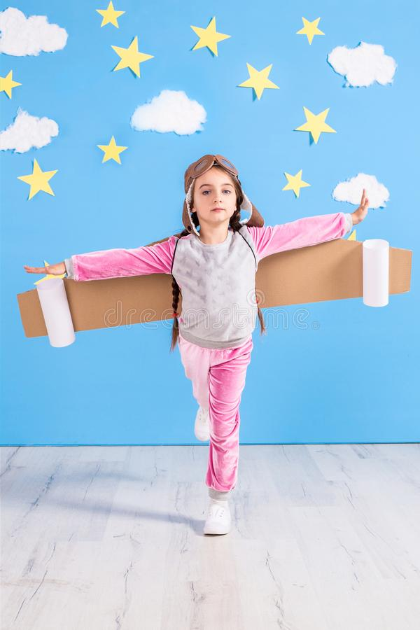 Jouer pilote de fille avec le paquet de jet de jouet à la maison Succès et concept de chef images stock