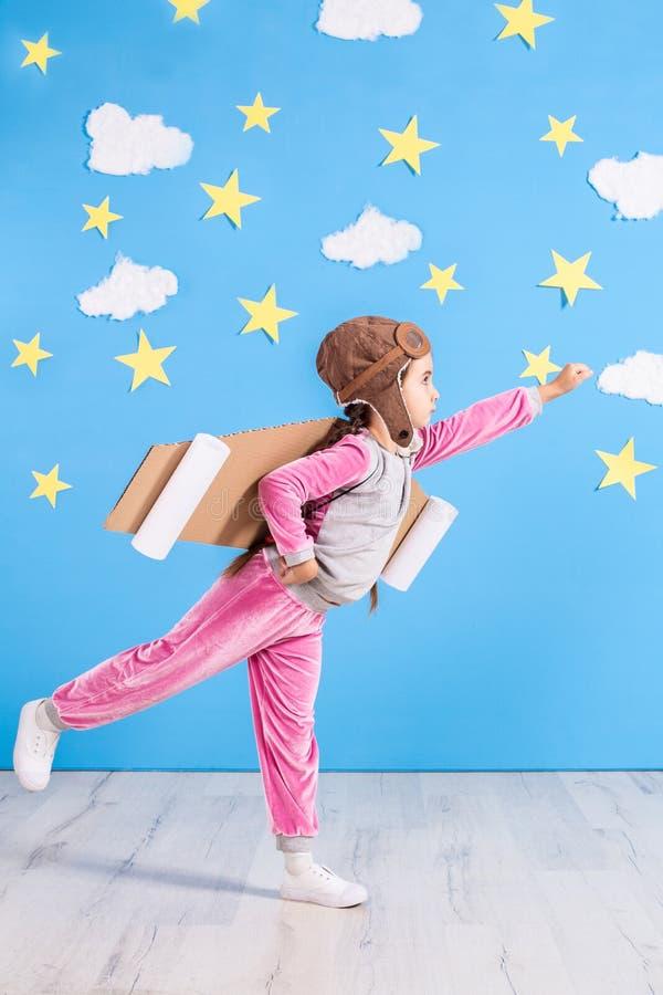 Jouer pilote de fille avec le paquet de jet de jouet à la maison Succès et concept de chef images libres de droits