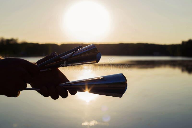 Jouer un agogo d'instrument de musique sur le ciel de fond au coucher du soleil photographie stock
