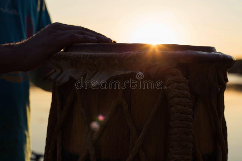 Jouer un jembe ou un atabaque d'instrument de musique sur le ciel de fond au coucher du soleil image stock