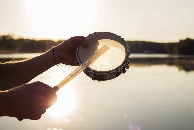 Jouer un tambour de basque d'instrument de musique sur le ciel de fond au coucher du soleil image libre de droits